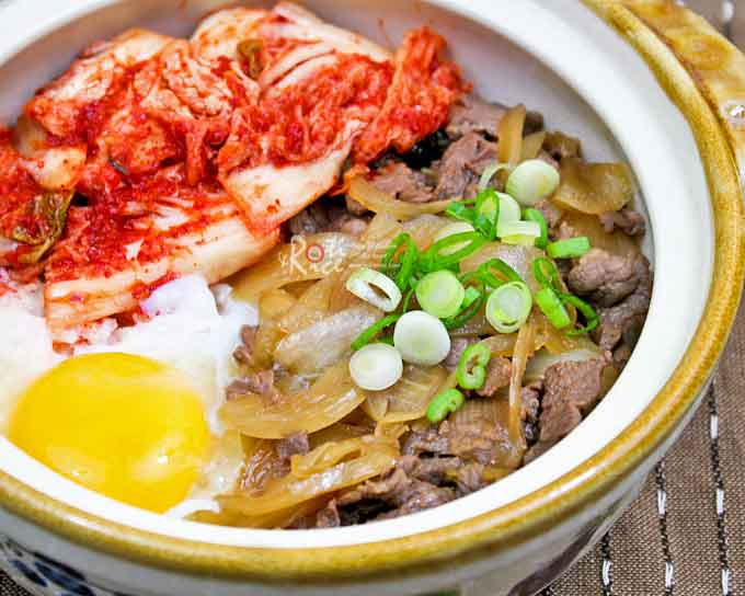 This flavorful Gyudon (Beef Bowl) topped with simmered beef, soft cooked egg, and cabbage kimchi makes a delicious and comforting meal. | RotiNRice.com