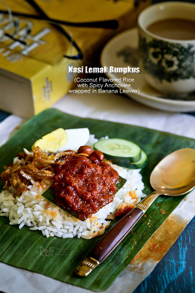 The ever popular and delicious Nasi Lemak Bungkus served with spicy anchovies, peanuts, hard boiled eggs, and cucumber slices wrapped in banana leaves. | RotiNRice
