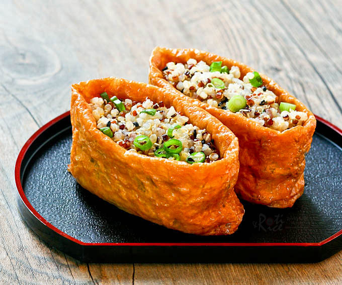 Delicious vinegar flavored Quinoa Filled Tofu Pockets resembling inari zushi. The tofu pockets are deep fried and seasoned with sweetened soy sauce. | RotiNRice.com