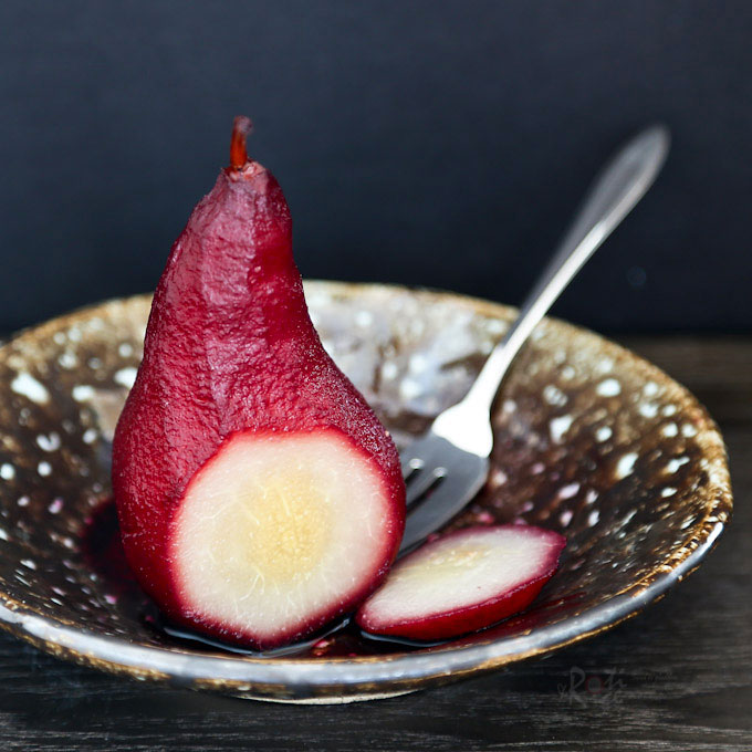 These Red Wine Poached Pears make an elegant and delicious dessert served with its reduced syrupy spiced poaching liquid. Definitely a must-try! | RotiNRice.com