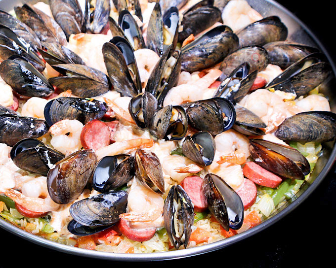 Fabulously tasty and attractive Seafood Paella with sausage, salmon, shrimps, and mussels. it is an experience you don't want to miss. | RotiNRice.com
